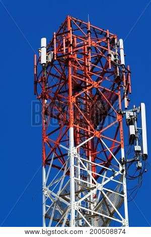 Mobile Phone Communication Antenna Tower With Satellite Dish On Blue Sky Background