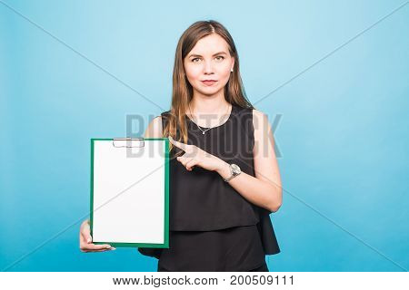 Portrait of young business woman holding a blank banner. image on a blue studio background. business and lifestyle concept