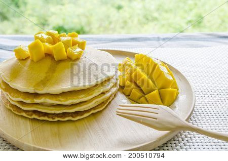 pancake with honey and mango on wooden plate