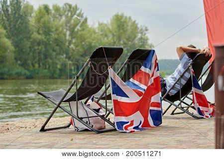 river landscape with four chaise longues and British flags on the beach