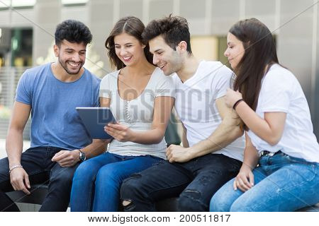 Laughing friends looking at tablet computer