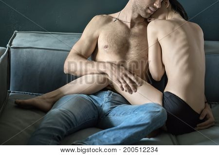 Tender topless couple is hugging on the sofa. Smiling guy wears blue jeans. Girl wears a black panties. Indoors. Closeup. Horizontal.