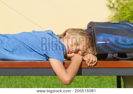 Tired schoolboy relaxing after school. Boy lying with closed eyes on the bench