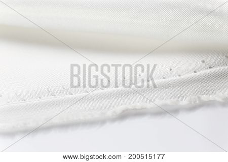 close up of folded shiny white fabric showing fabric's edge good for luxyrious or romantic theme background room for copy space