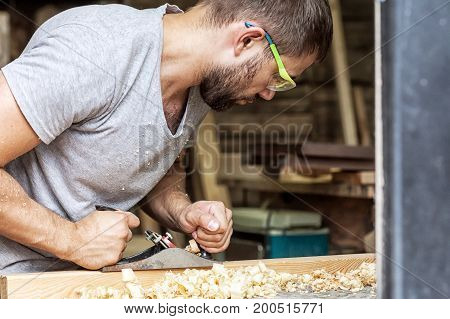 Man Handles A Wooden  With A Black Jack Plane