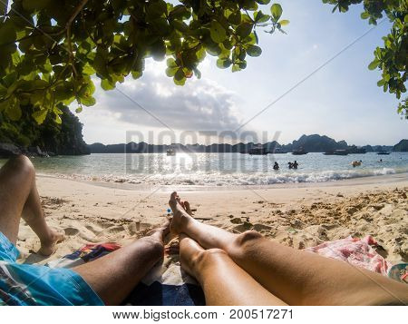 legs of couple relaxing on a sandy tropical beach - holiday concept
