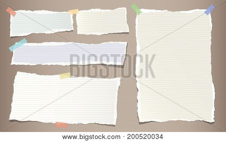 Colorful pastel, ripped note, copybook, notebook paper strips stuck with sticky, adhesive tape on brown background