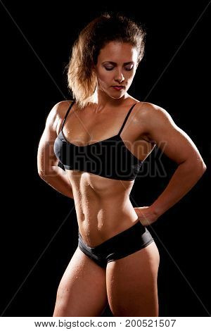 Beautiful sporty muscular woman on black background.