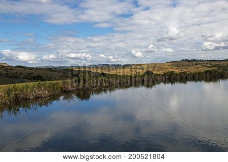 Dam Reflecting Blue Cloudy Winter Sky In Country Landscape