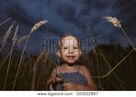 Cute baby girl playing hide and seek at dusk