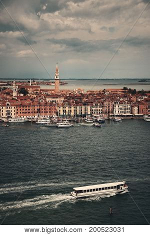St Marks church clock tower and city skyline with boat viewed from San Giorgio Maggiore island in Venice, Italy.