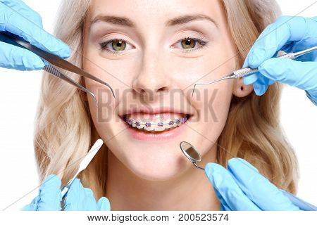 Portrait of a smiling woman with braces with hands holding dentist tools near her face.