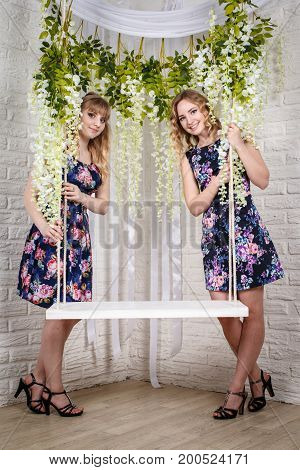 Two Blond Sisters, Swing And Flowers