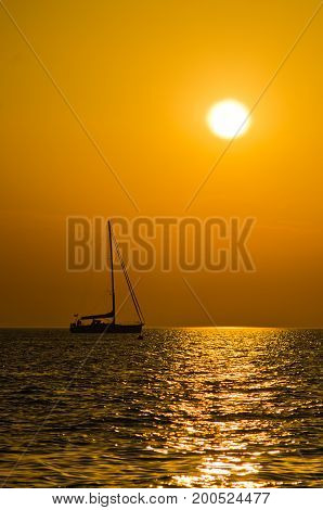 Silhouette of a yacht on a sea surface at sunset in Greece