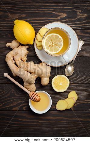 Ginger root tea with lemon and honey on wooden background, top view