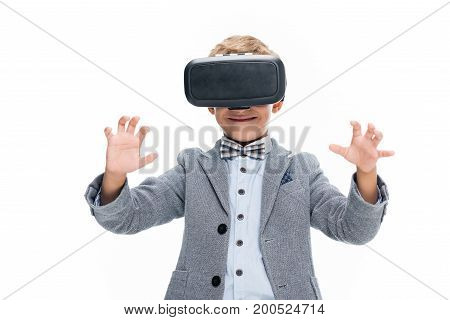 schoolboy in VR headset pretending to touch something isolated on white