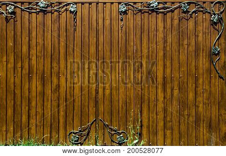 Wooden fence with wrought iron ornate, background