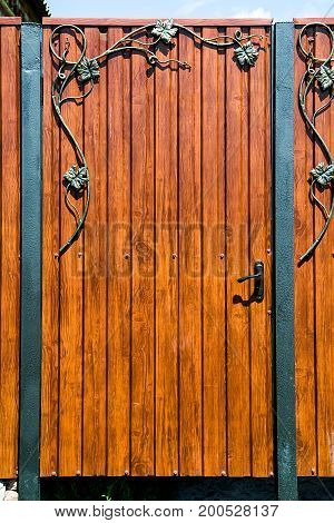 Rustic wooden gate with wrought iron ornate