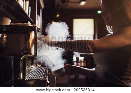 Close-up image of female barista using coffee-making machine to steam milk in cafe.