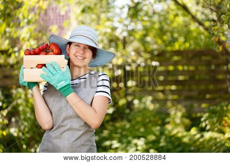 Portrait of girl in hat with tomato box in garden