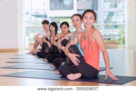 Yoga Class In Studio Room,group Of People Doing Seated Half Lord Of Fishes Poses ,relaxation Sport W