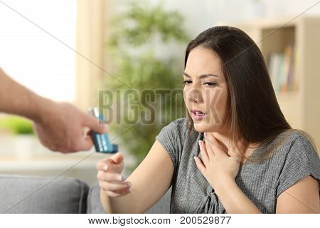 Asthmatic girl suffering an asthma attack receiving an inhaler at home