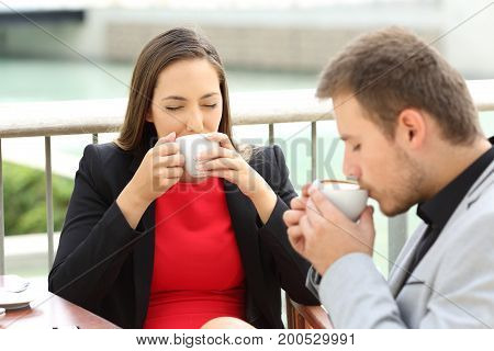 Two happy executives drinking coffee cups sitting in a bar terrace
