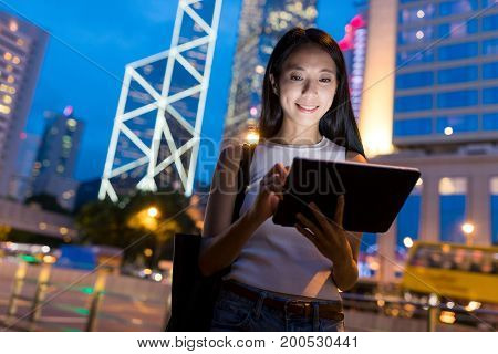 Business woman working on tablet computer at night
