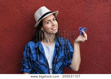 happy girl playing with fidget spinner. Portrait of young woman holding spinner. Popular trendy stress relieving toy