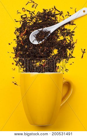 Falling driedn teain cup on yellow background white background
