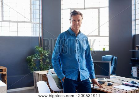 Portrait of a casually dressed mature businessman smiling confidently while standing alone by his desk in a large modern office