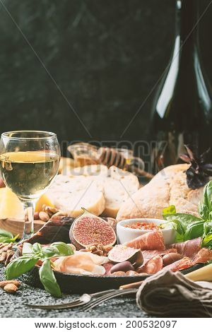 Italian antipasti wine snacks set. Cheese variety, nuts, Mediterranean olives, sauces, Prosciutto di Parma or jamon, and wine over dark background