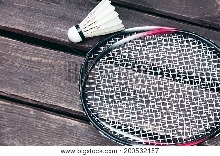White shuttlecock and badminton rackets lie on a wooden background