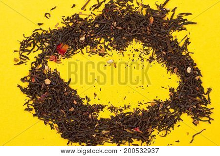 Aromatic tea with fruit petals on the yellow background