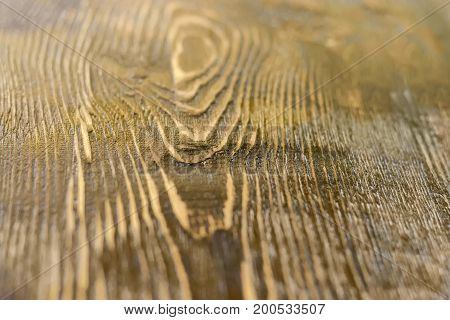 Background of a surface of the old wooden plank darkened with time at shallow depth of field