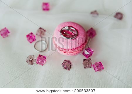 Wedding rings on the pink macaron with pink gems on white background