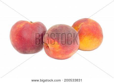 Three ripe fresh peaches on a white background