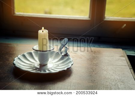 closeup of candle and old candle holder by the window