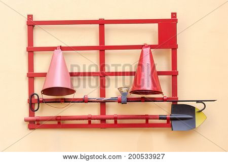 Red fire stand with fire extinguishing tools: conical fire buckets fire ax hook and spade hanging on a yellow wall