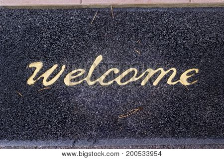 Old wet shabby doormat with the word welcome and with pine needles stuck in it on a porch