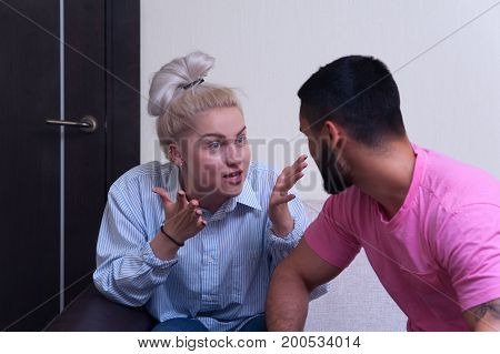 Young couple quarrelling at home. Depressed frustrated woman yelling at her boyfriend.