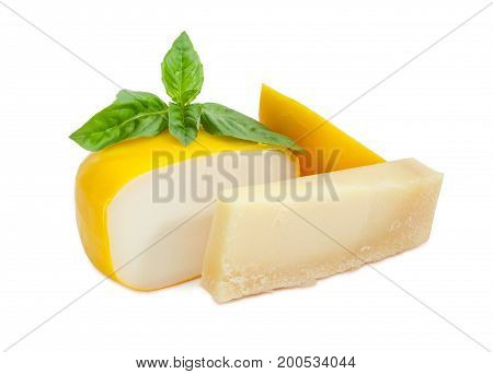 Piece of the parmesan cheese and partly sliced small wheel of firm goat cheese with twig of green basil on a white background