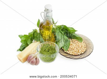Sauce basil pesto in the small glass bowl and ingredients for its preparation on a white background