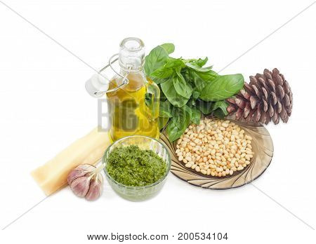 Sauce basil pesto in the small glass bowl on a background of ingredients for its preparation and pine cone on a white background