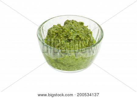 Sauce basil pesto in the small glass bowl on a white background