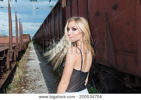 Beautiful blonde girl walking on rail tracks, romantic look, from back, wind in the hair