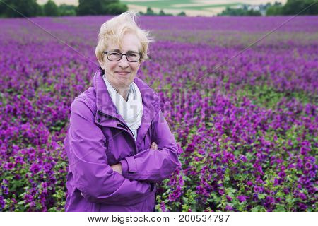 older woman standing in front of purple flower feild and smiling at camera