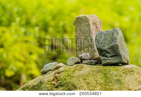 Two large rectangle shaped rocks on top of a large boulder with a green soft blurred background.