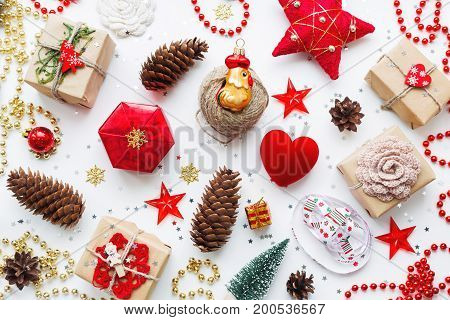 Christmas background with decorations. Gifts in craft paper pine cones red hearts and confetti. Flay lay top view.