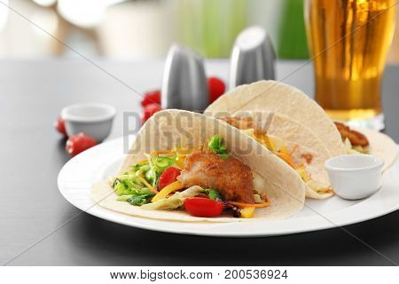 Delicious fish tacos served on white plate on table